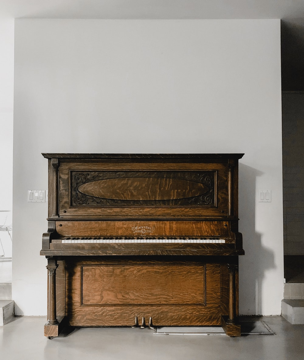 brown wooden upright piano beside white wall
