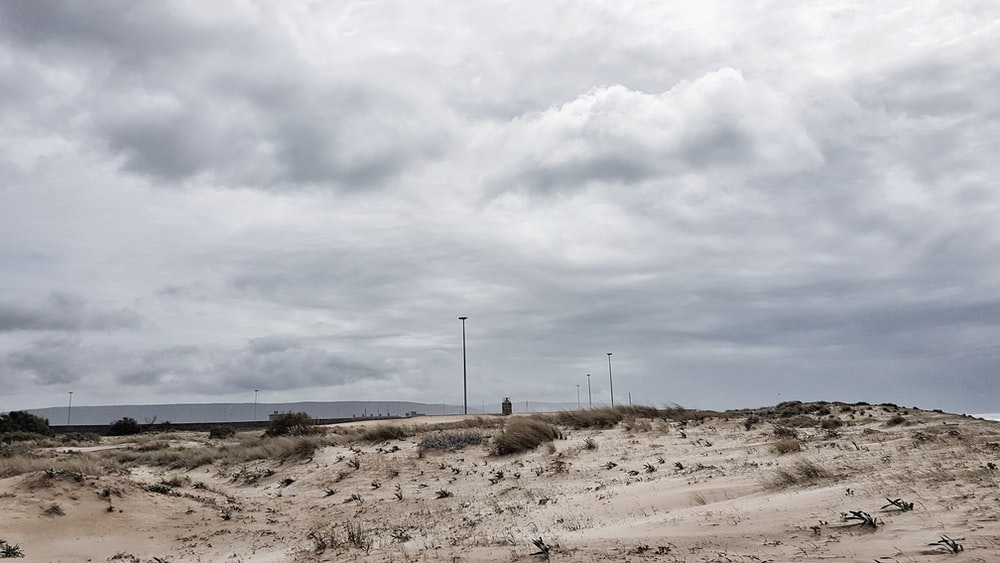 grey cloudy sky over brown desert