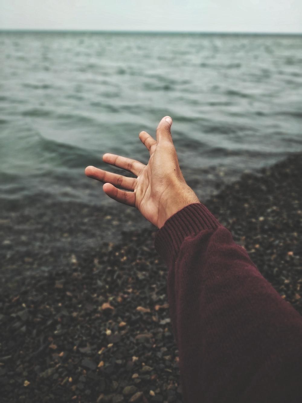 person raising hand near body of water