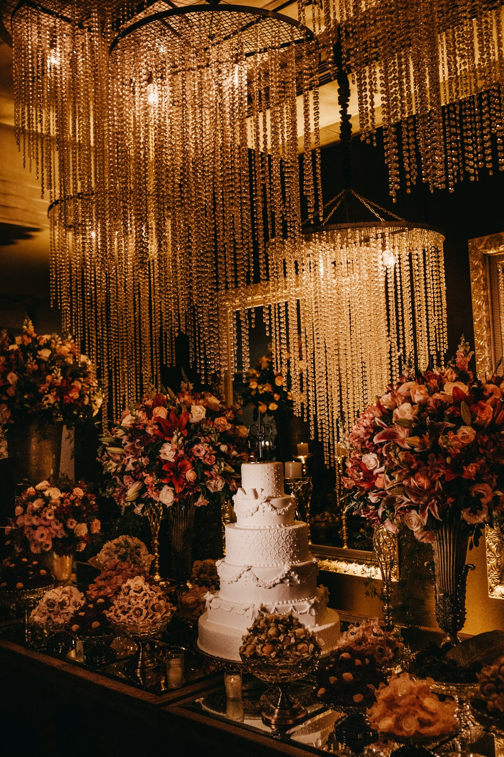 5 layer wedding cake surrounded with assorted-color flower arrangement with lighted chandeliers