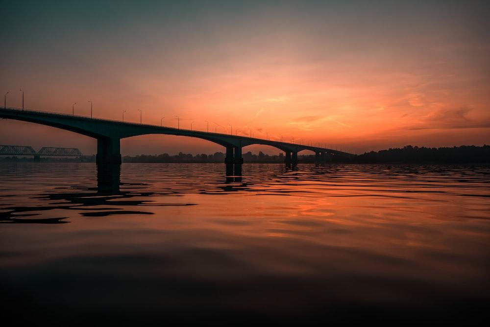 concrete bridge viewing sea under orange skies