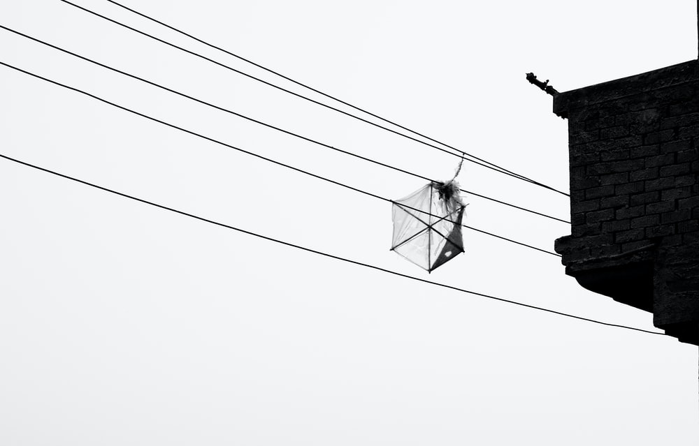 grayscale photo of cable wire near building