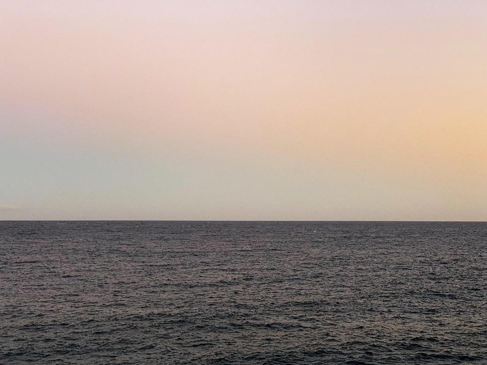calm body of water under orange skies