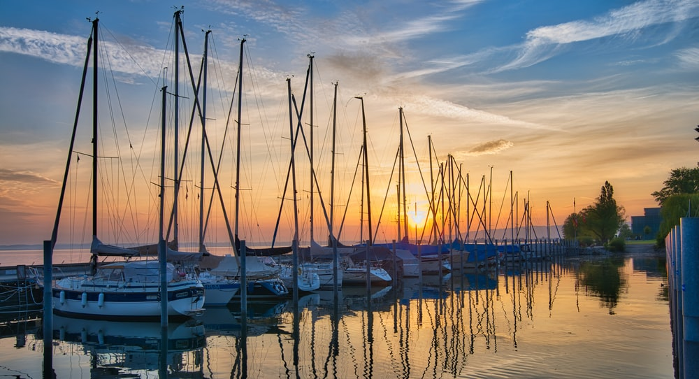 different yachts on sea under sunrise