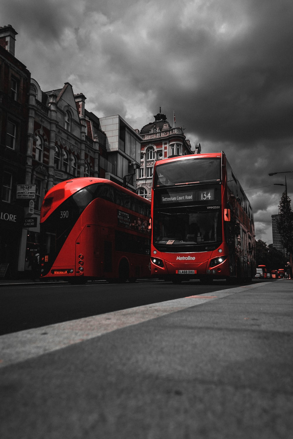 red and black bus on road near concrete buildings