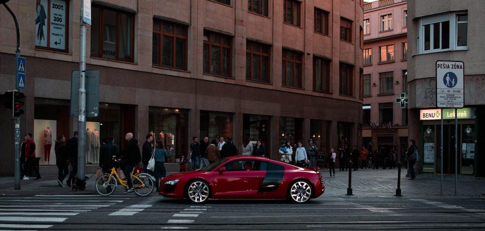 red sedan on road near people walking beside concrete buildings