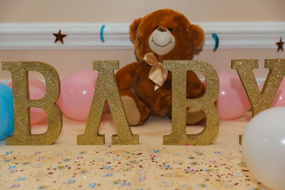 baby freestanding letters near brown teddy bear