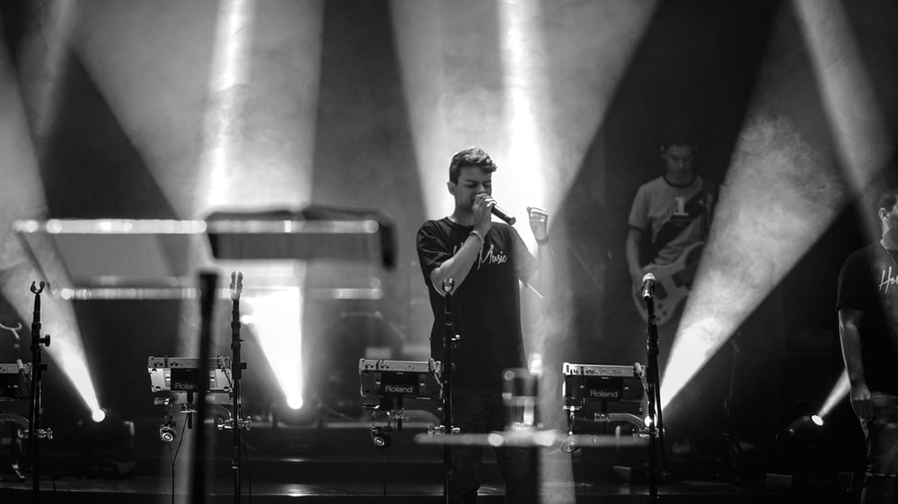 grayscale photo of man performing on stage