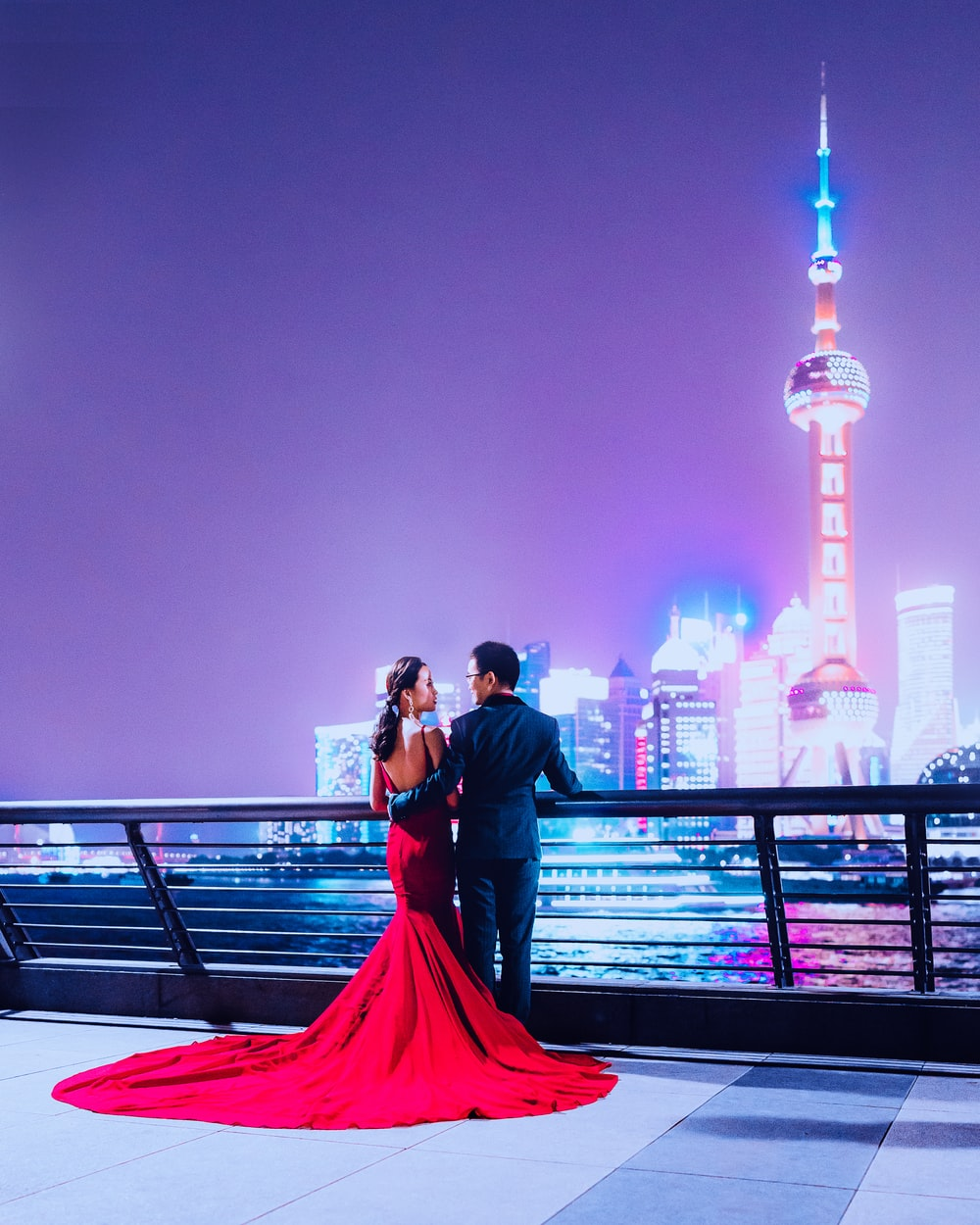man and woman standing beside rail facing on Oriental Pearl Tower during nighttime