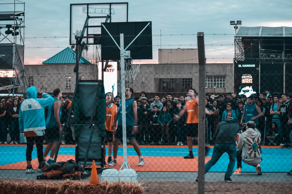 group of men playing basketball surrounded with many people
