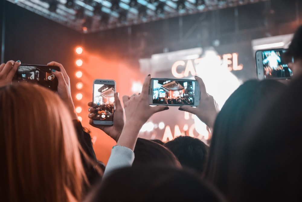 group of people holding smartphone displaying camera