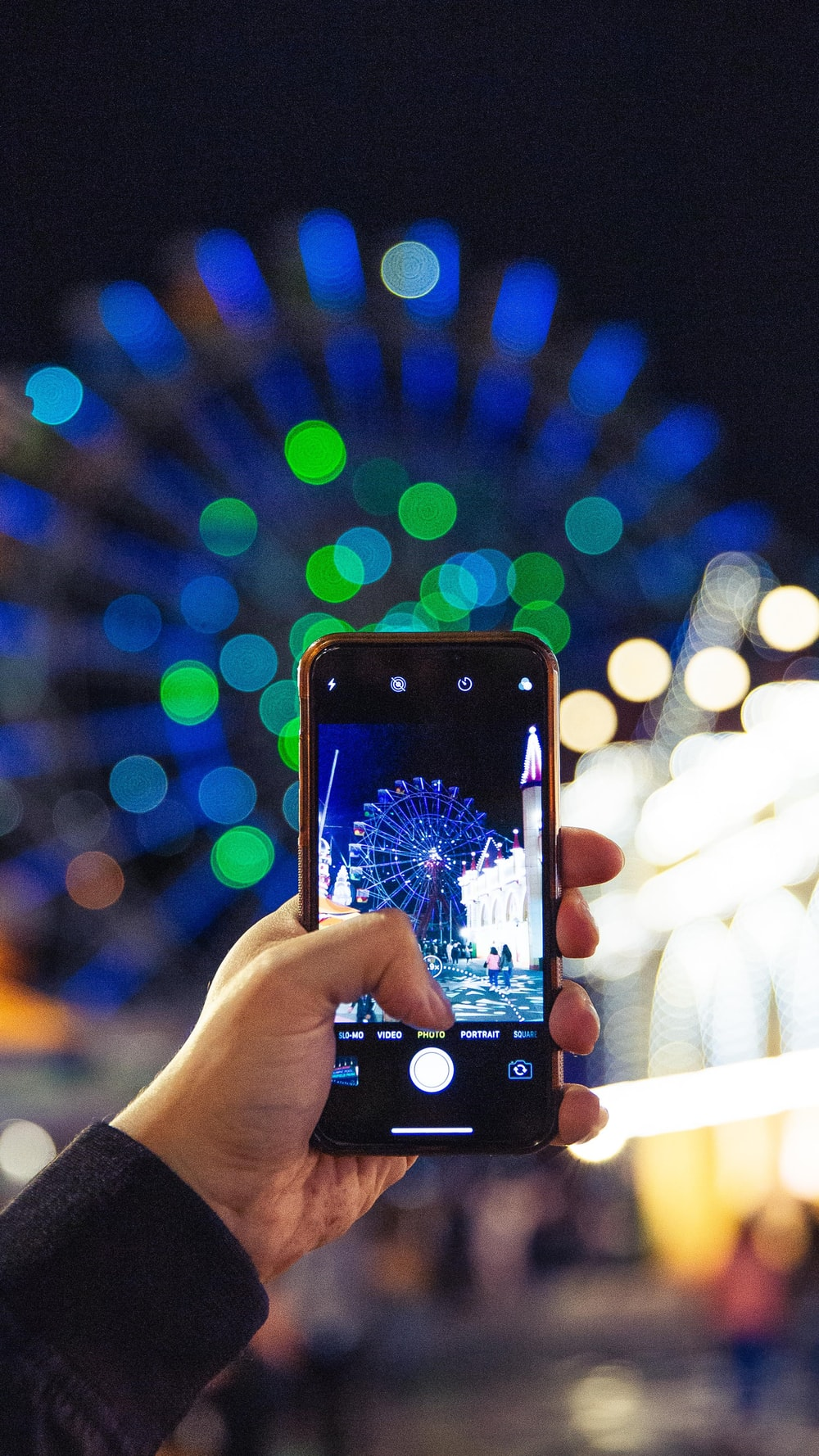 person holding smartphone displaying camera flashing the Ferris wheel