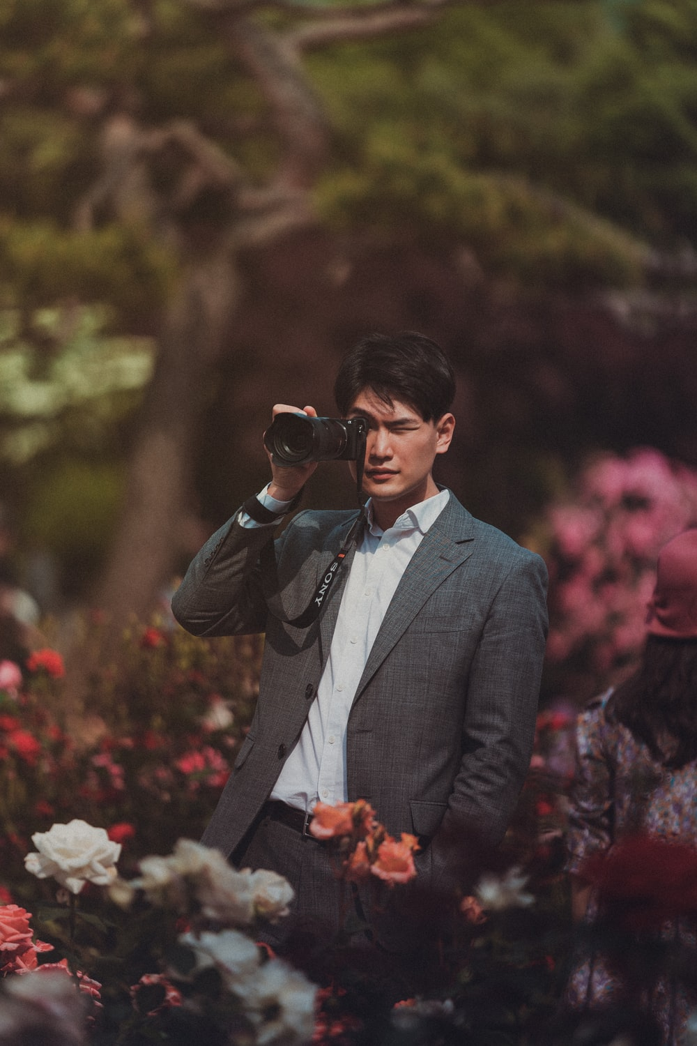 man standing and using DSLR camera in the middle of flower garden