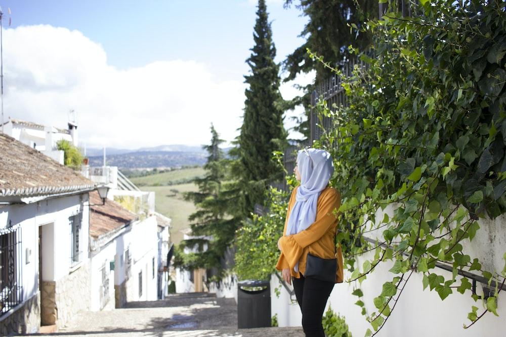 woman standing on road near plants