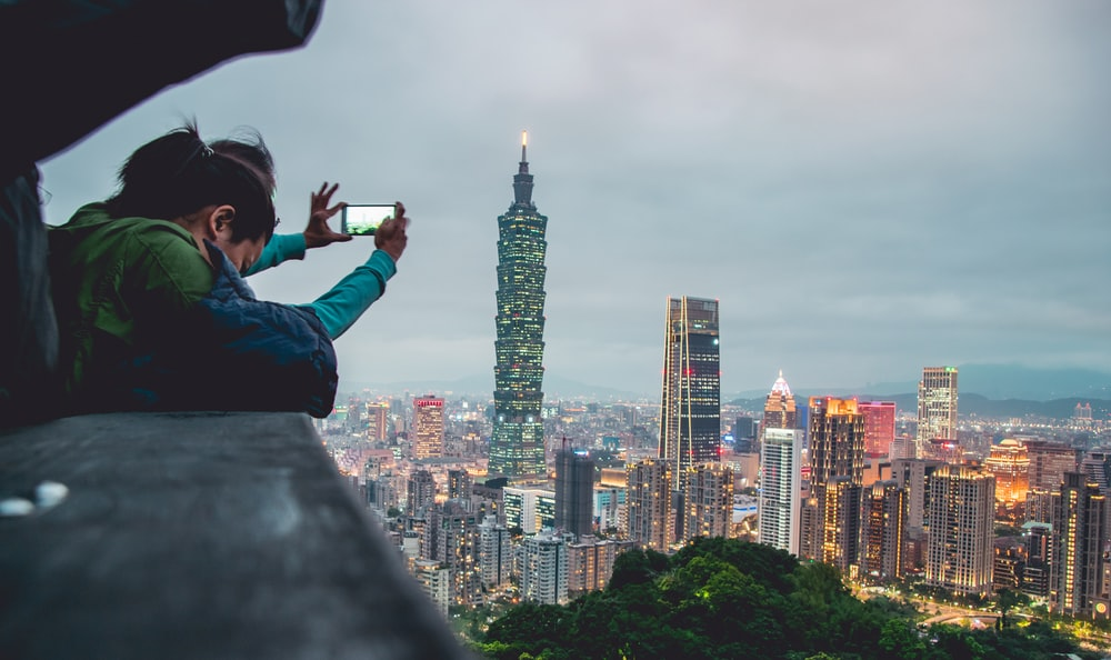 person who holding smartphone taking photo of Taipei 101 during daytime
