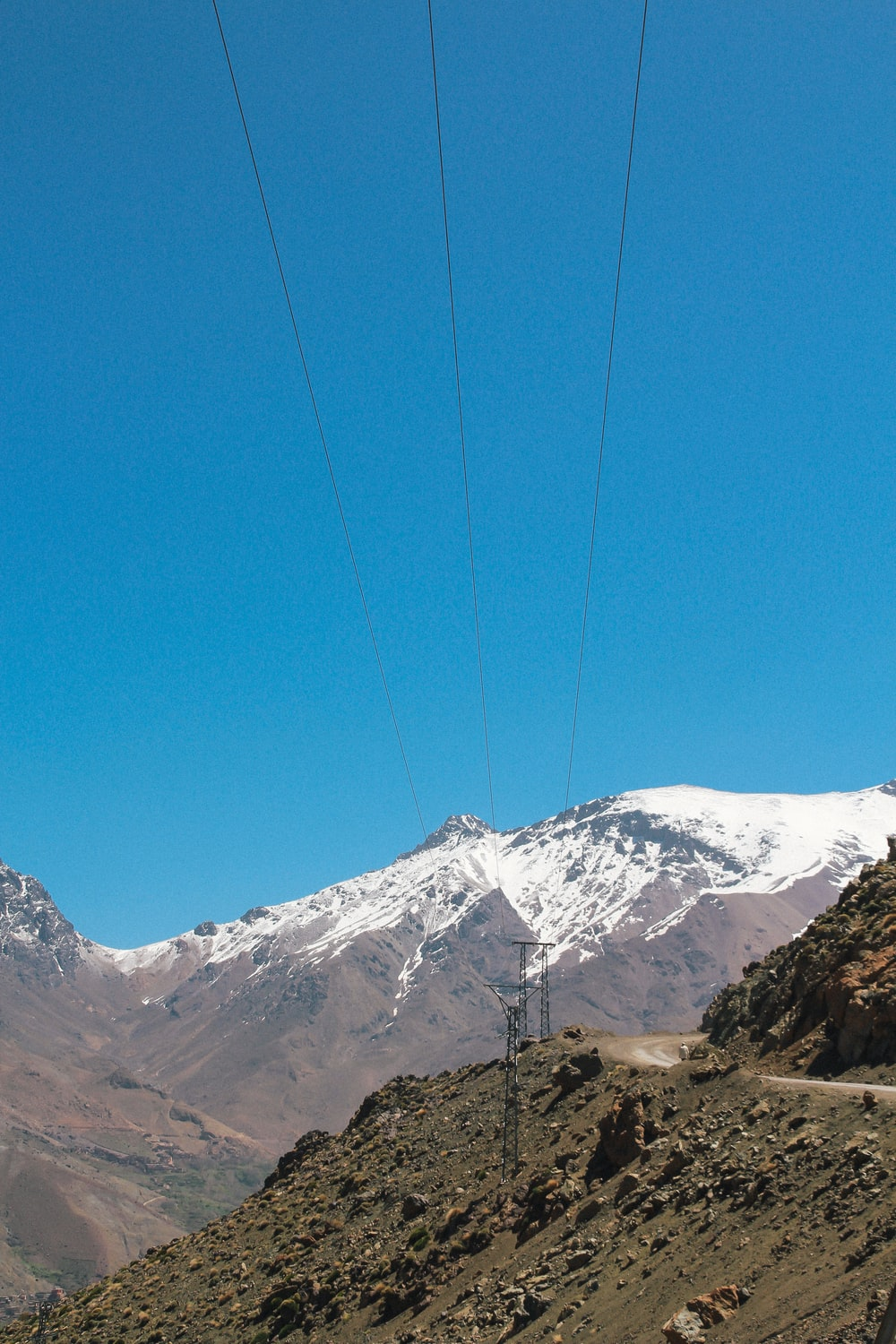 power transmission lines on mountain slope under clear blue sky