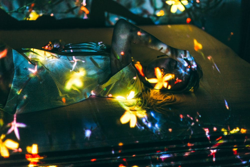 woman lying on bed with reflection of flowers