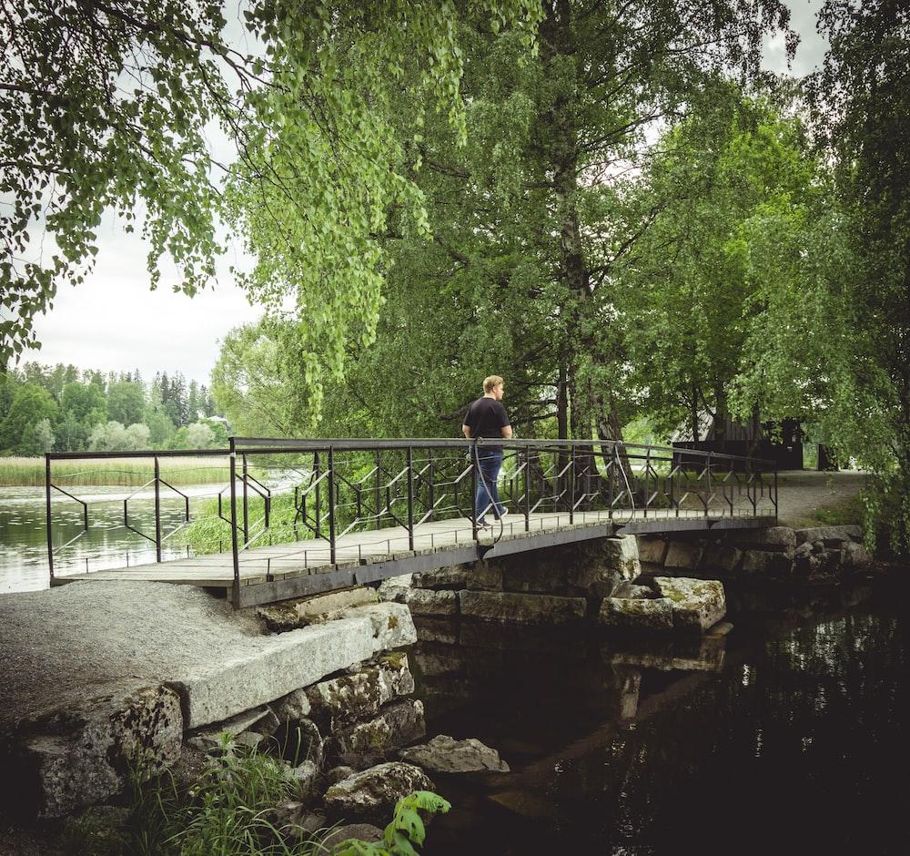 man walking on bridge near trees