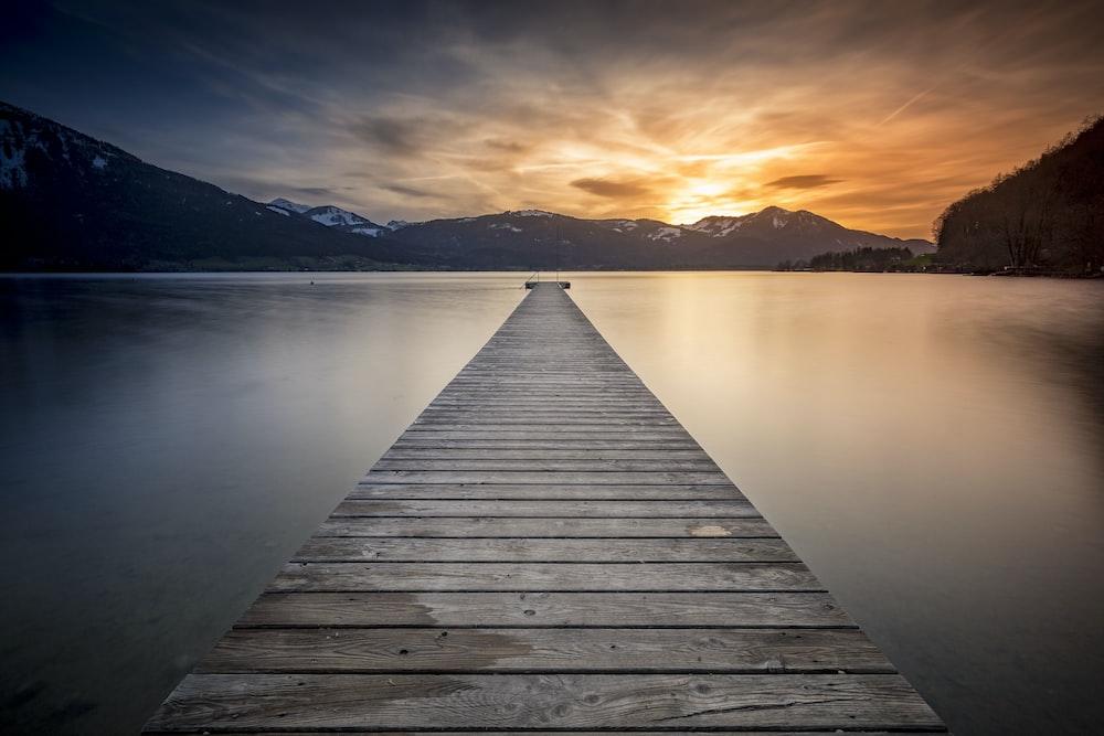 empty gray wooden boardwalk during golden hour