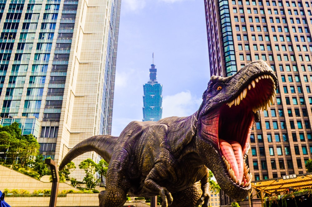 dinosaur with open mouth beside buildings still selective focus photography of