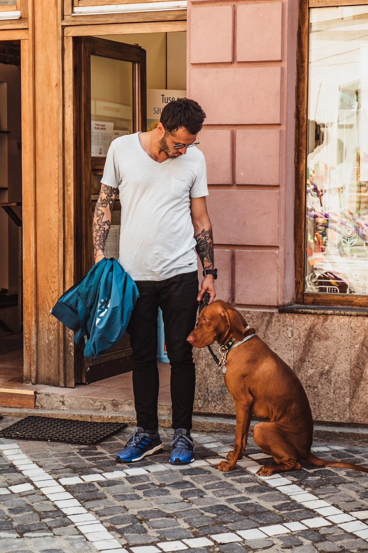 man standing beside sitting dog near open door of building