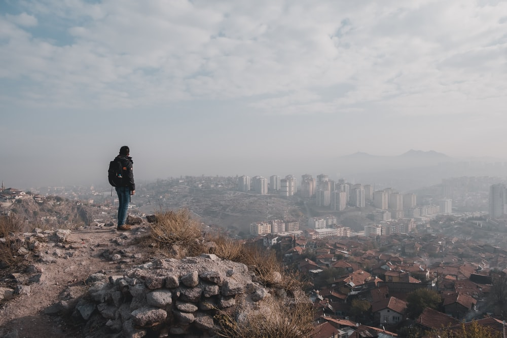man standing on top of hill overlooking city