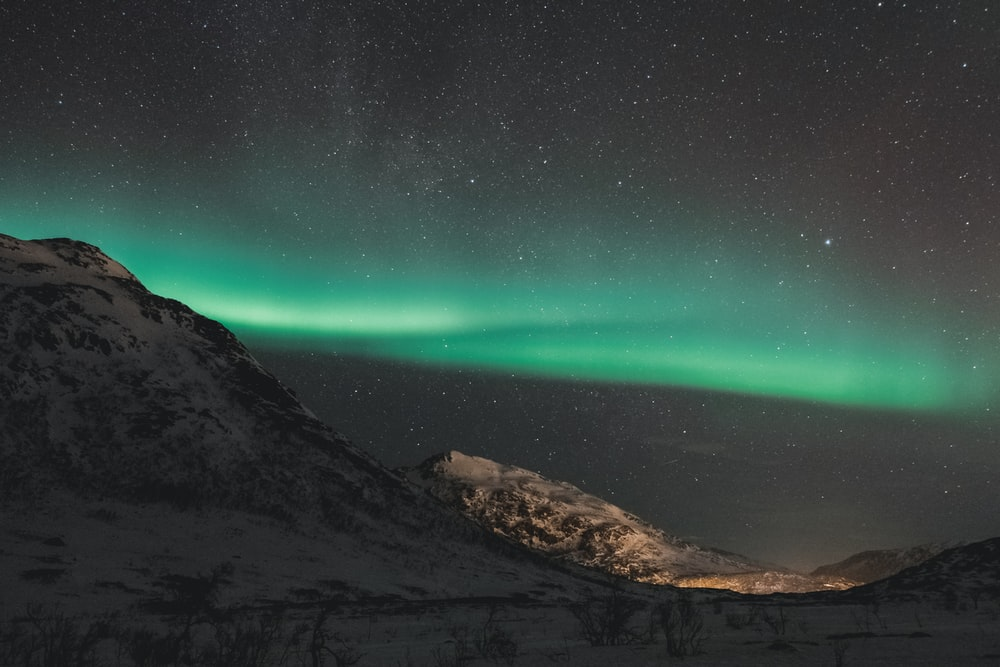 snow covered hill under green starry sky