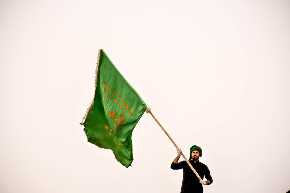 man standing while holding green flag