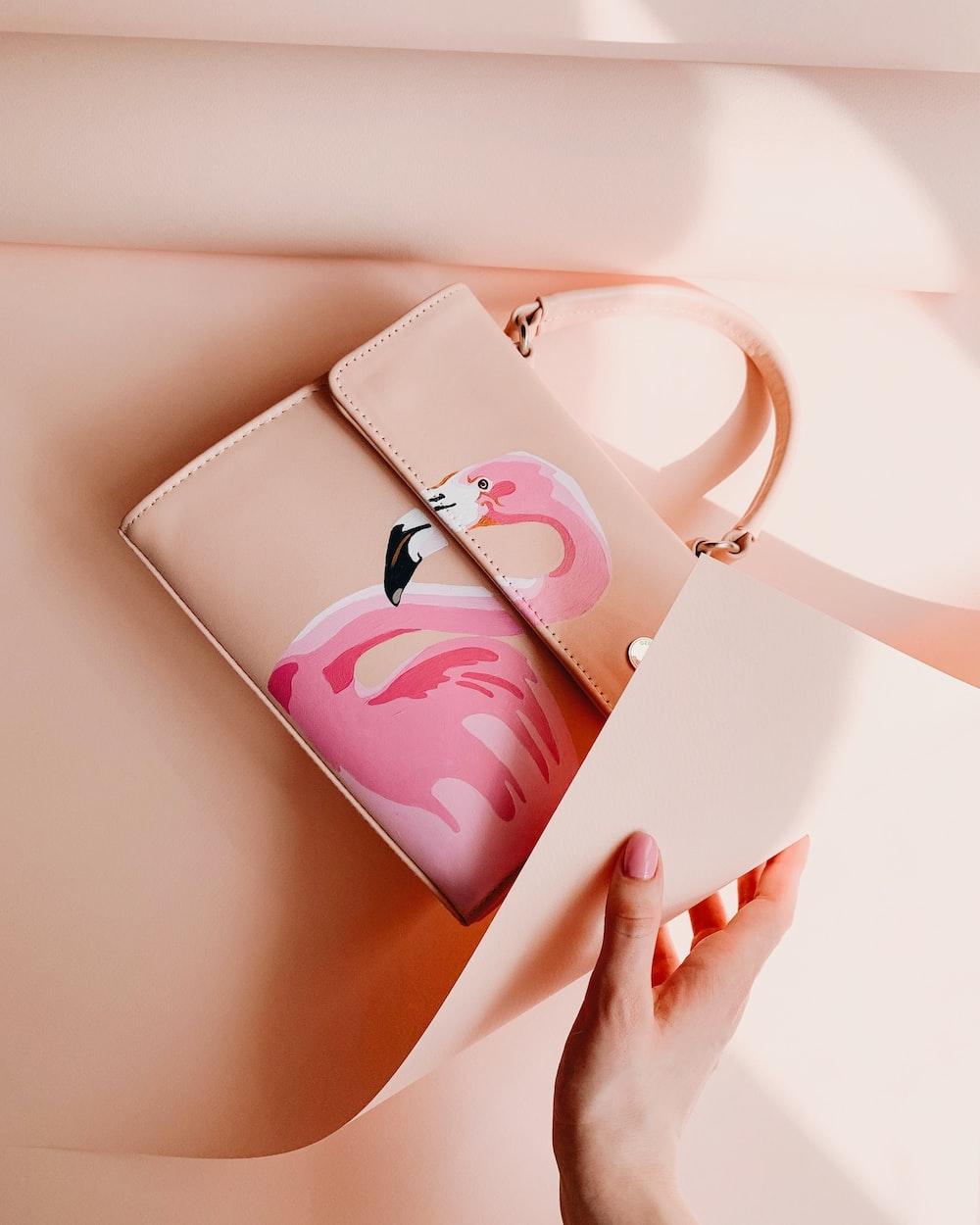 person wrapping pink flamingo graphic handbag