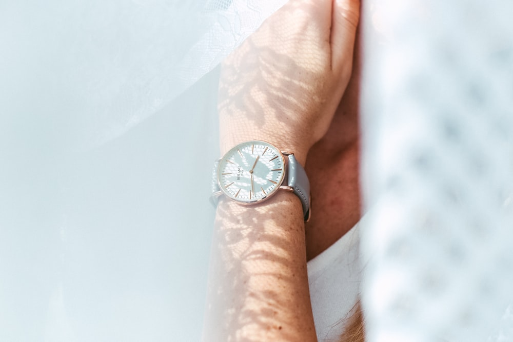 person wearing round white analog watch