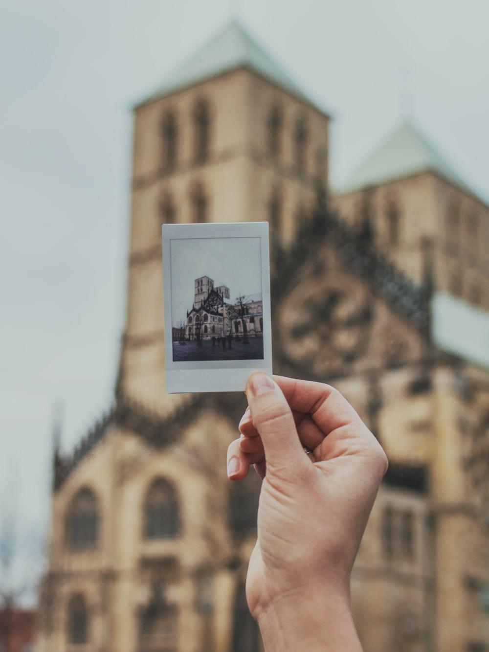 person holding brown concrete building photo