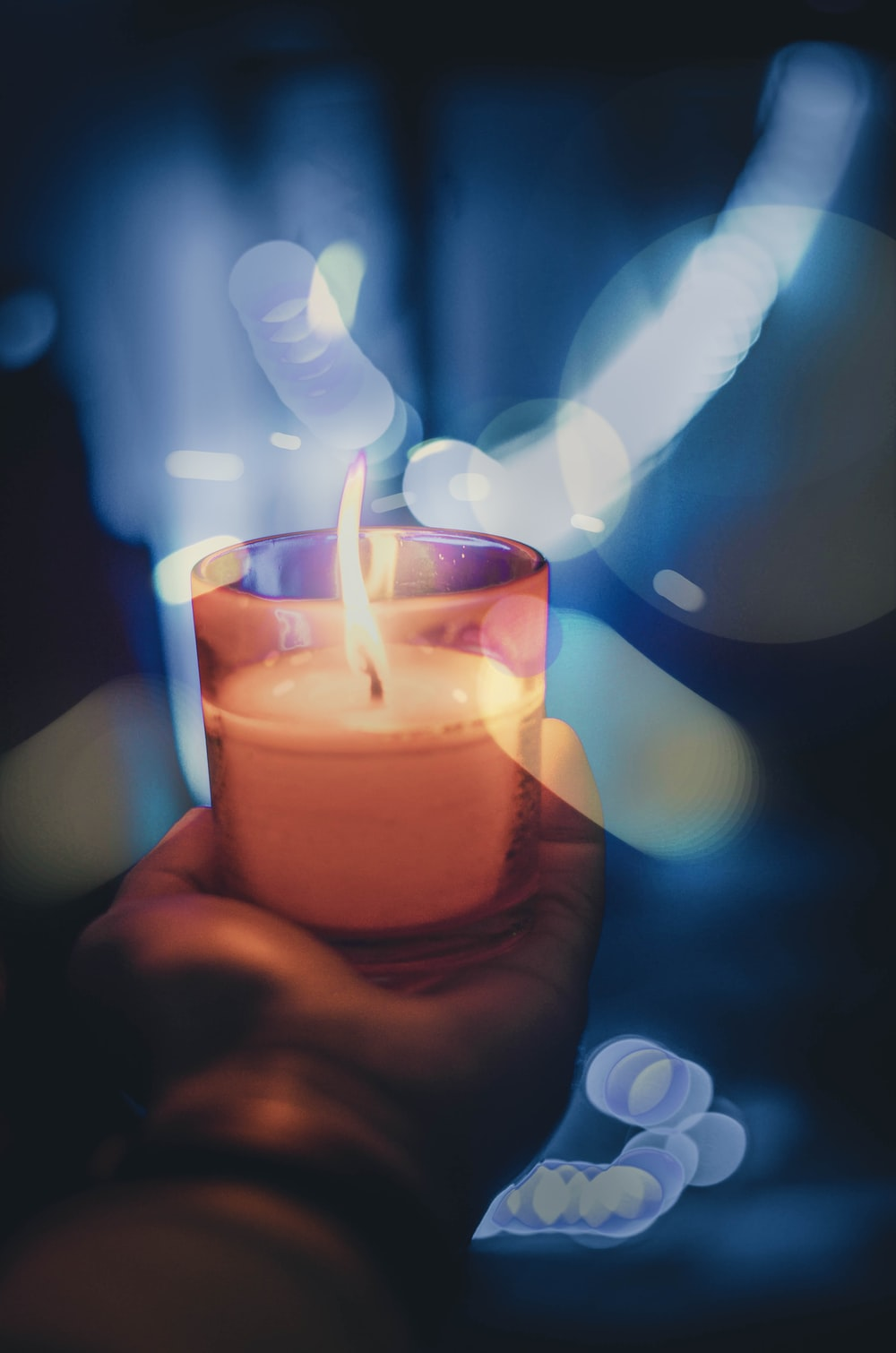 person holding lighted votive candle