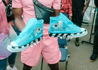 man holding blue-and-white Converse All-Star high-top sneakers