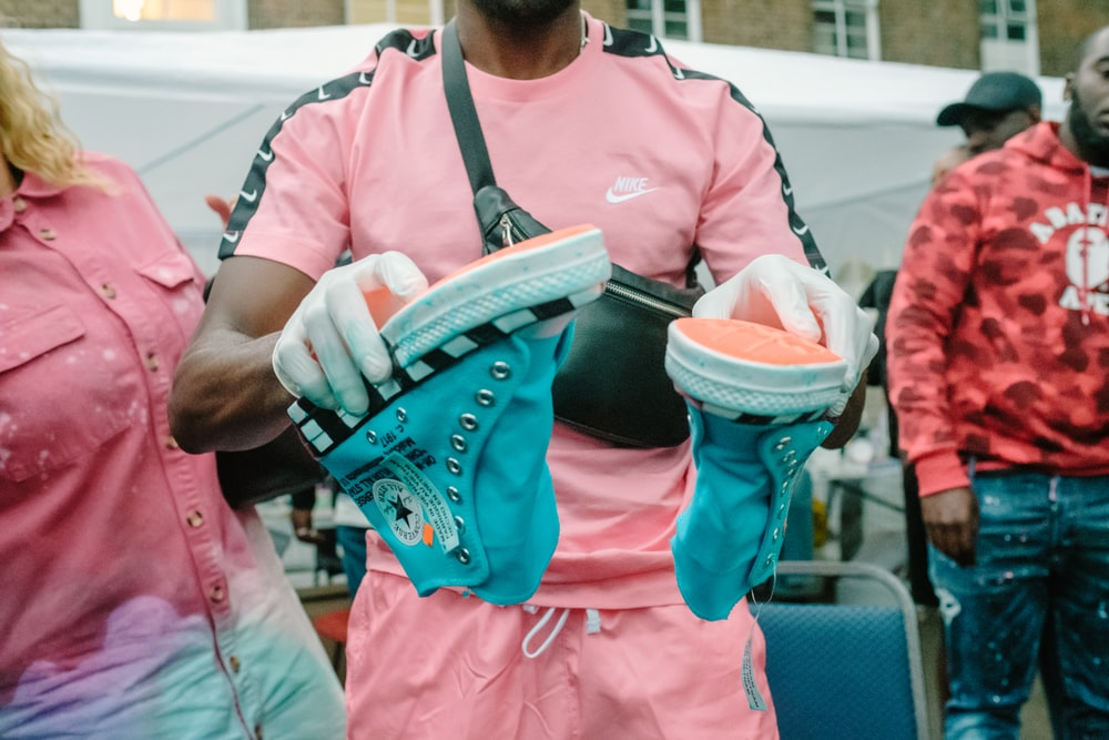 person holding pair of teal high-top sneakers