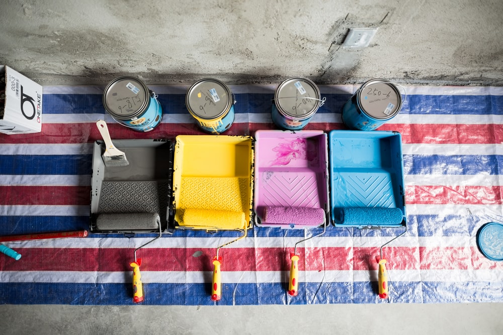 four assorted-color paint cans beside container and paint rollers