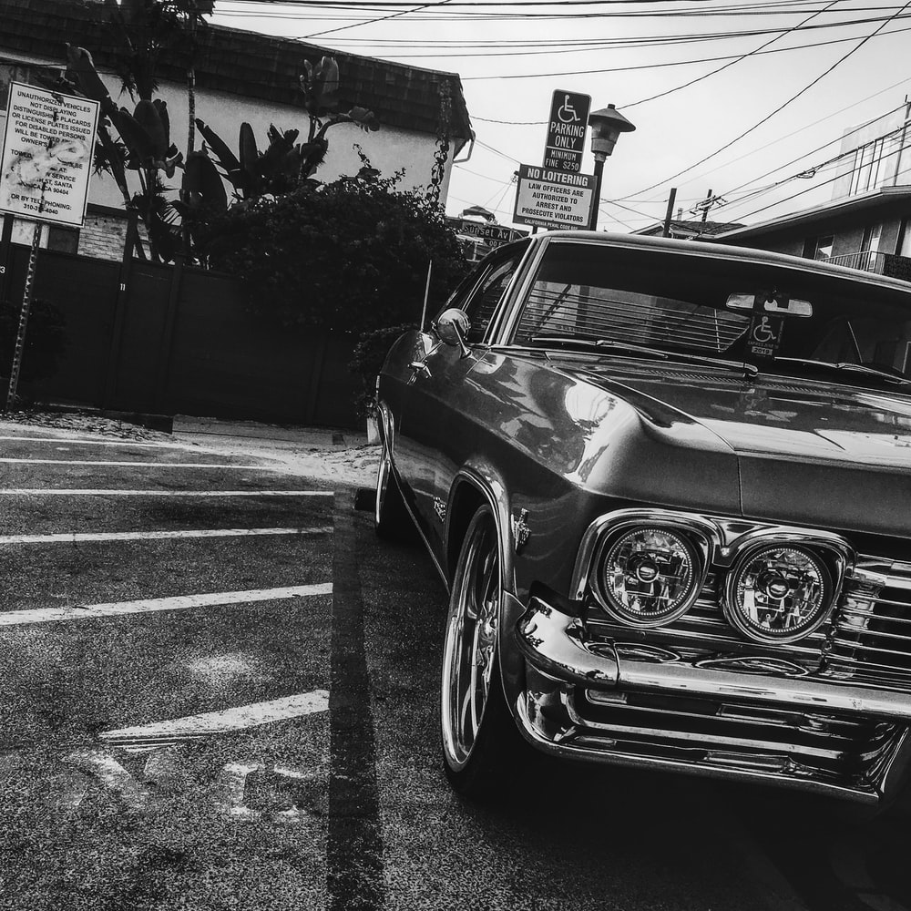 grayscale photography of car on parking area