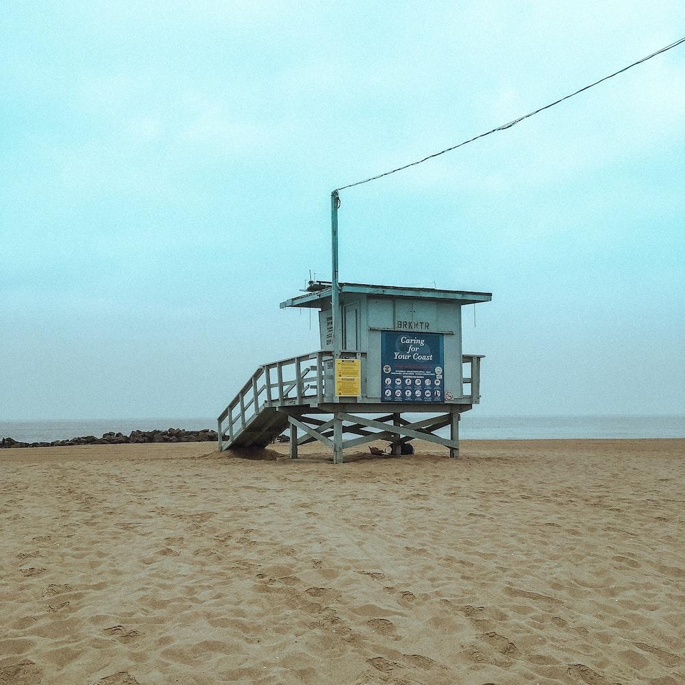 white lifeguard house on shore under blue sky