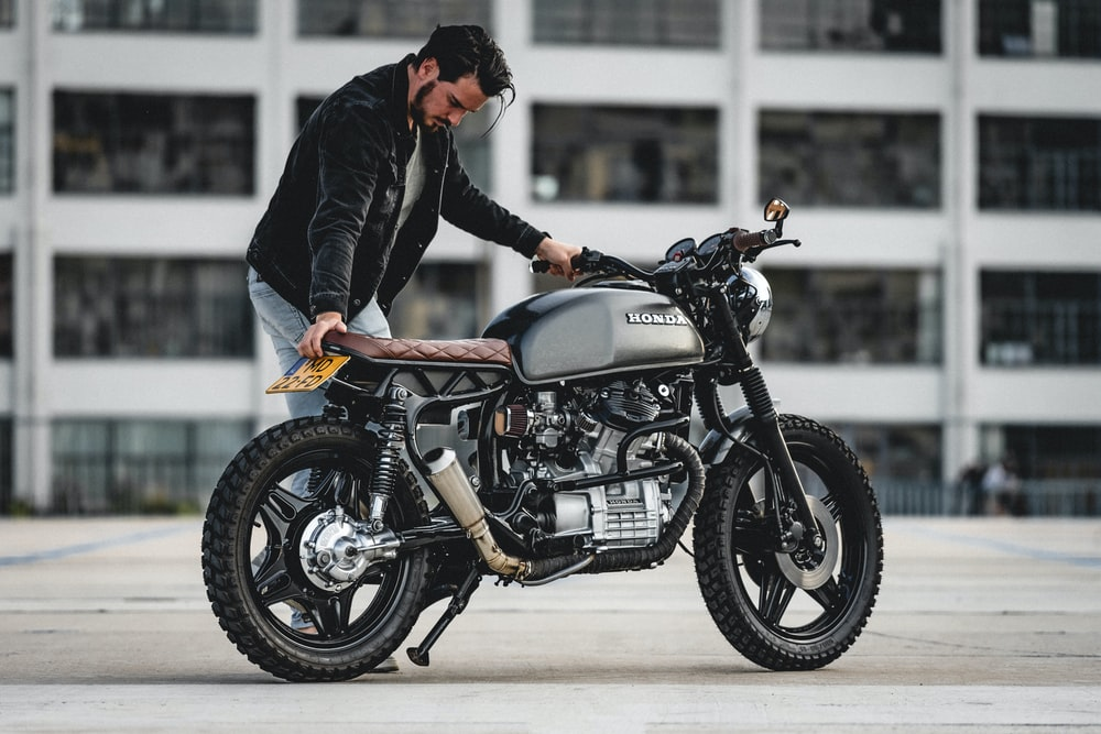selective focus photography of man holding motorcycle