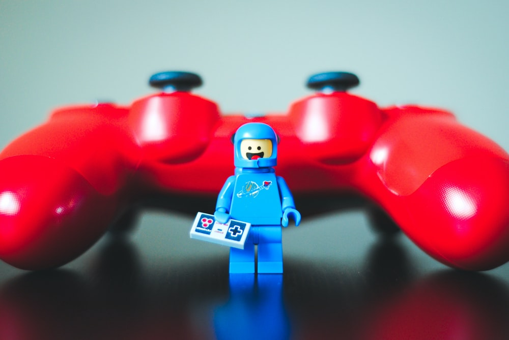 blue lego toy beside red game controller