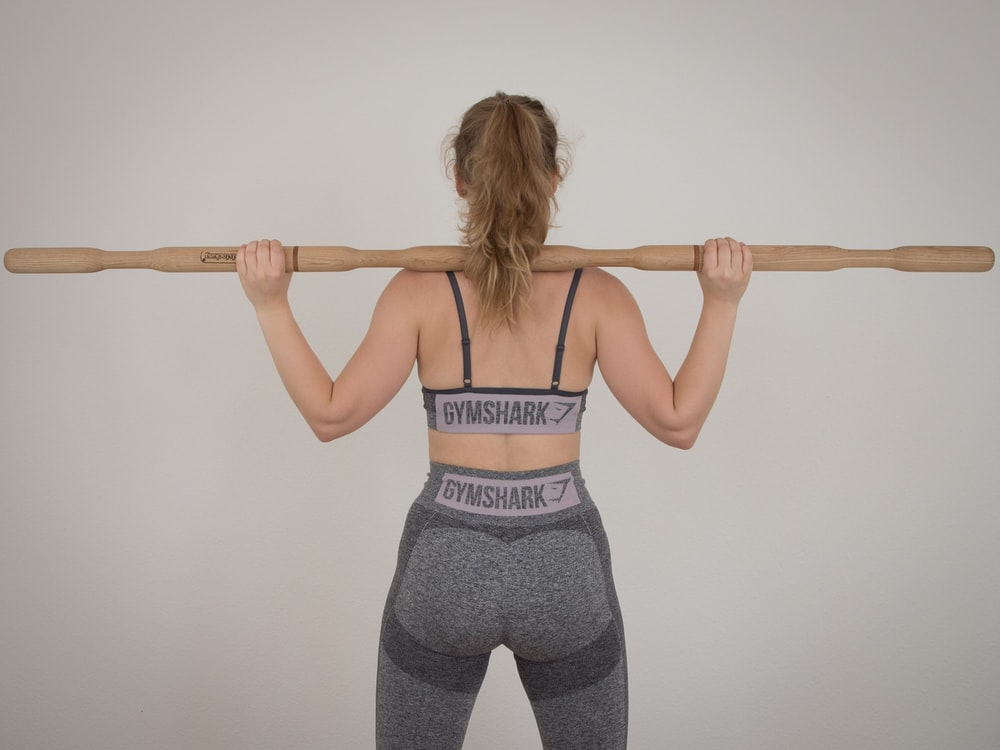 woman in gray sports bra and leggings carrying wooden weight bar on shoulders