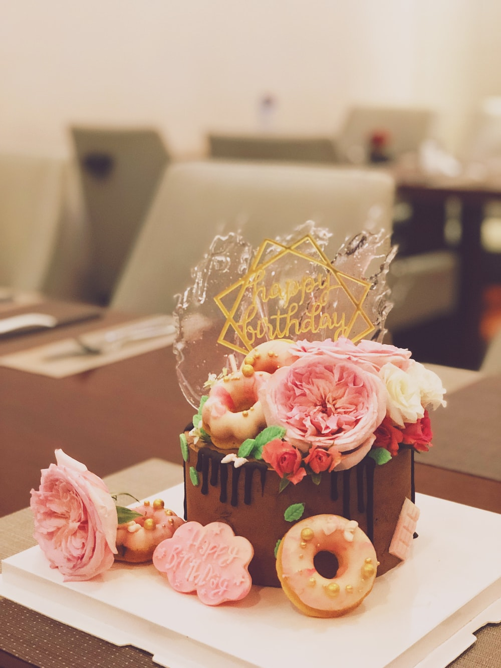 chocolate cake topped with roses and doughnuts