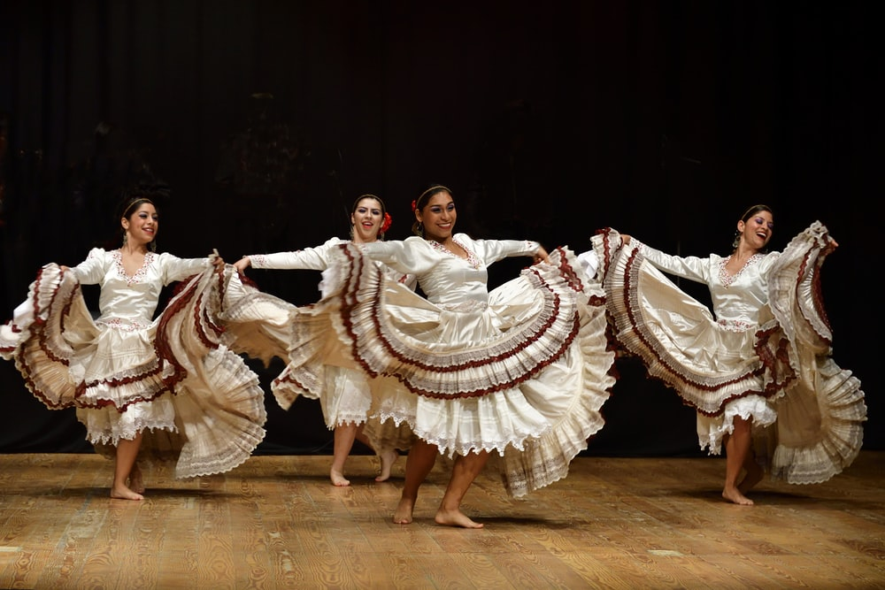 four women barefooted dancing on stage