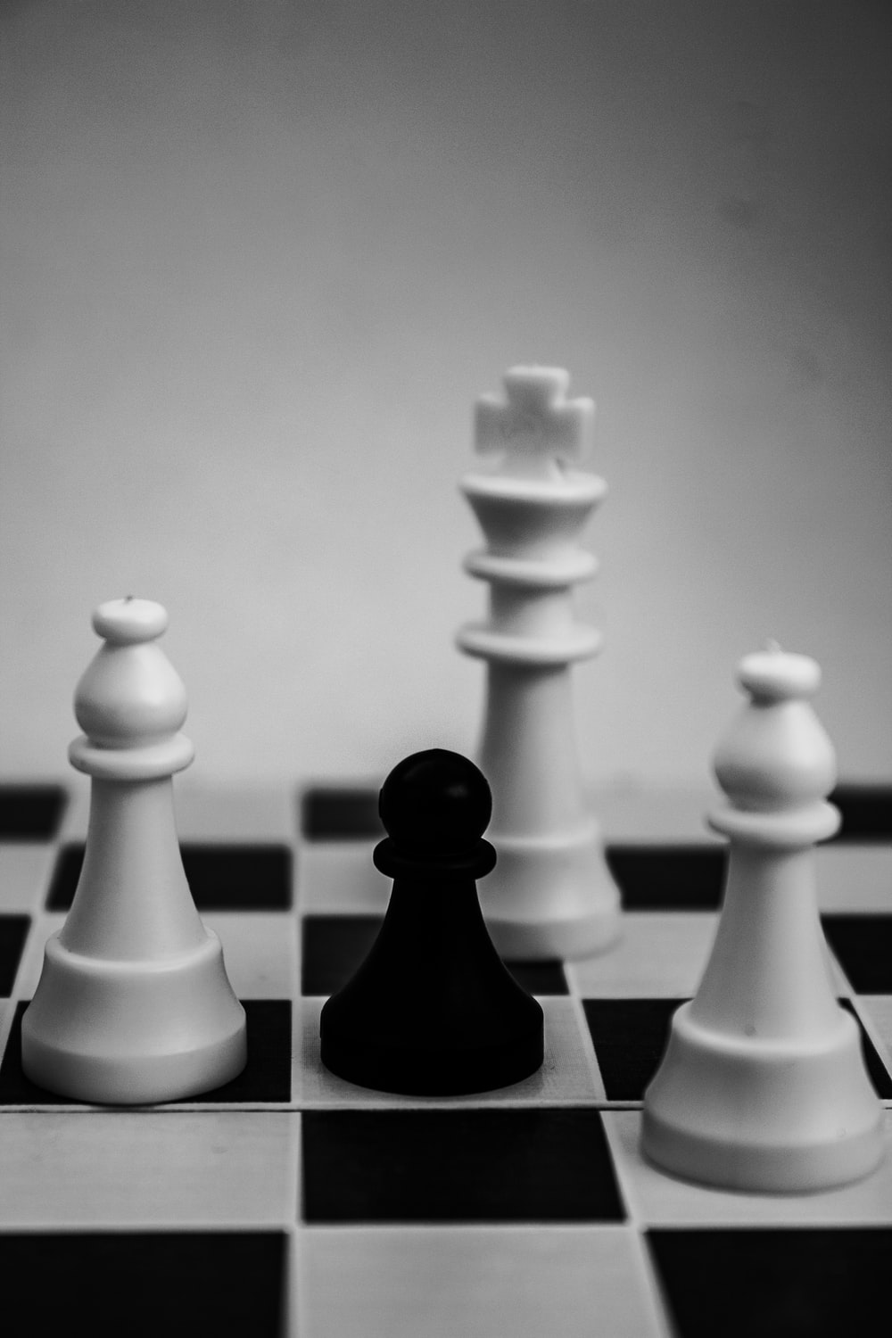 grayscale photo of king, pawn, and bishop chess pieces
