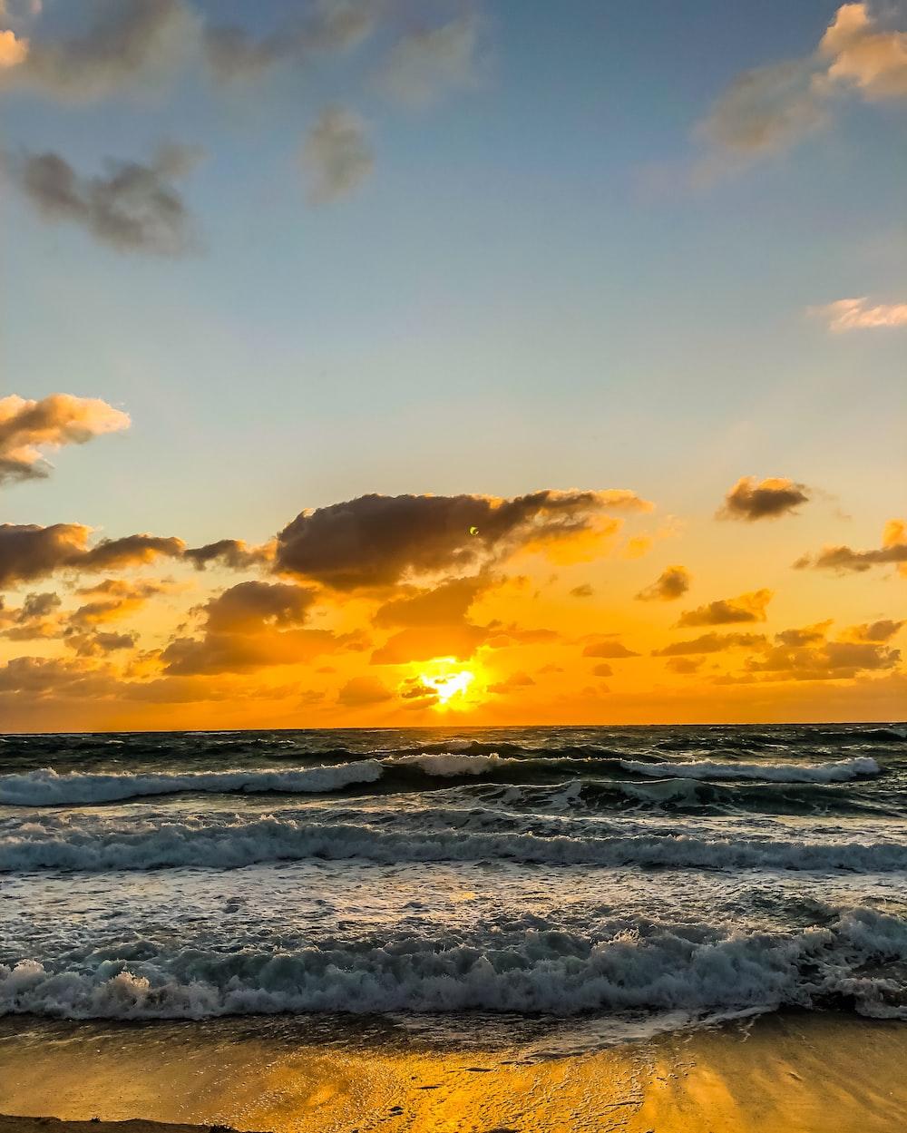 calm sea under orange and blue skies