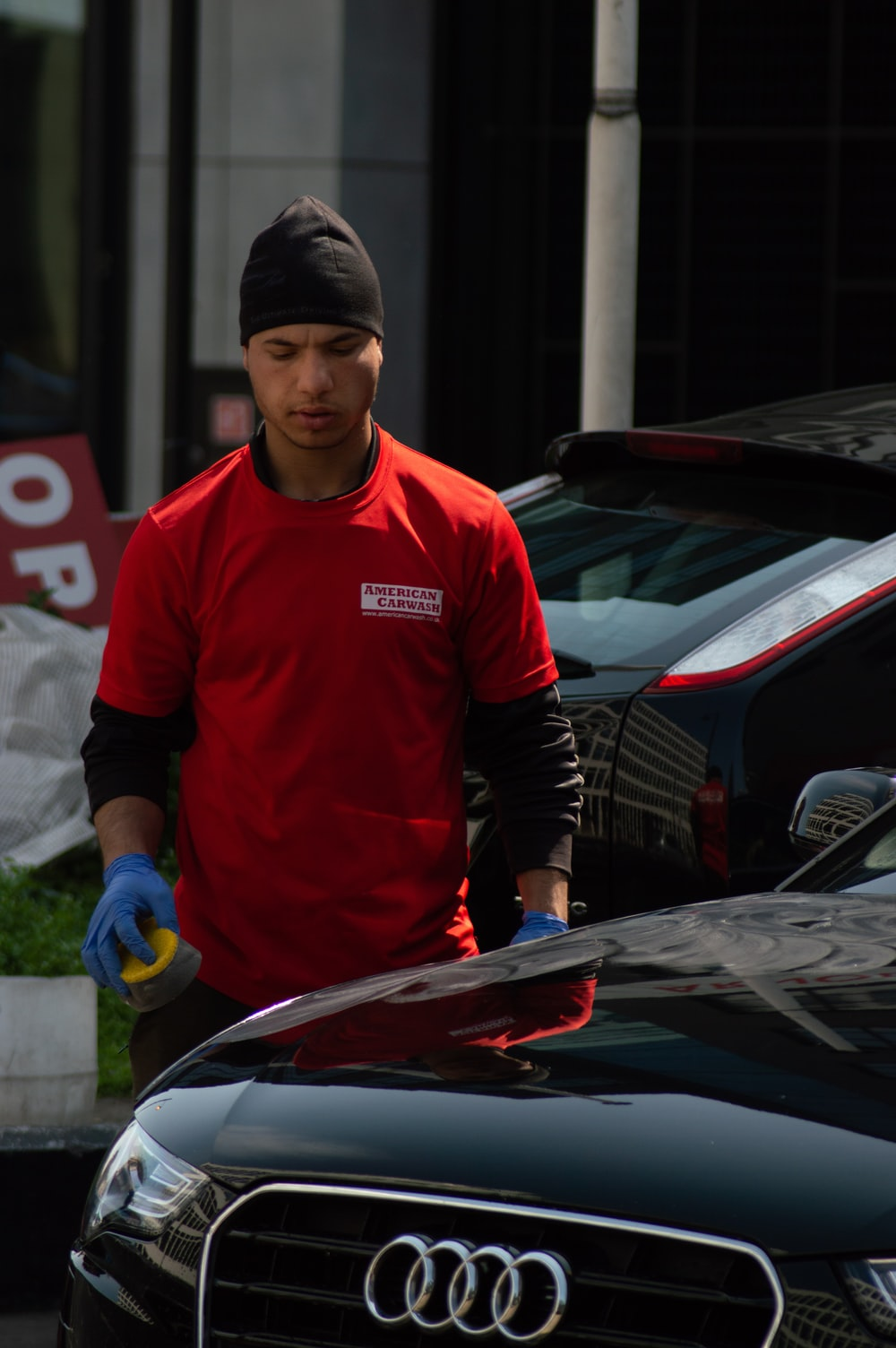 man standing beside black Audi car