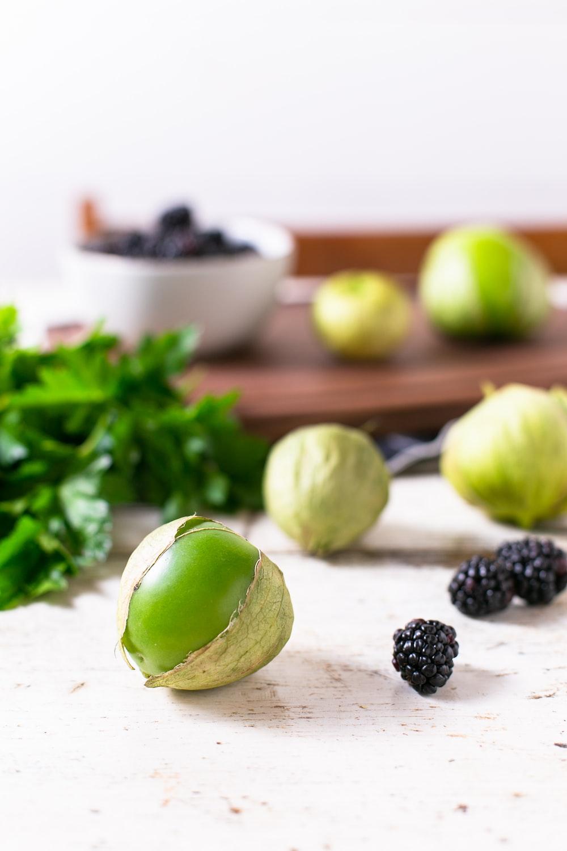 green fruit near black berry on white surface, avocado salsa