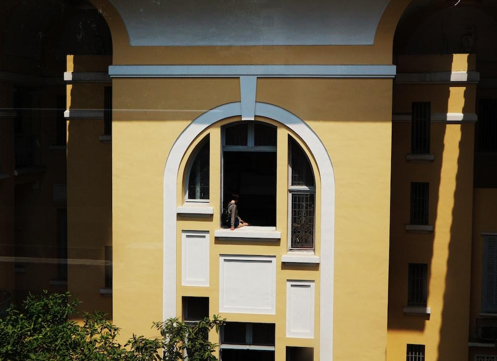person sitting on window panel