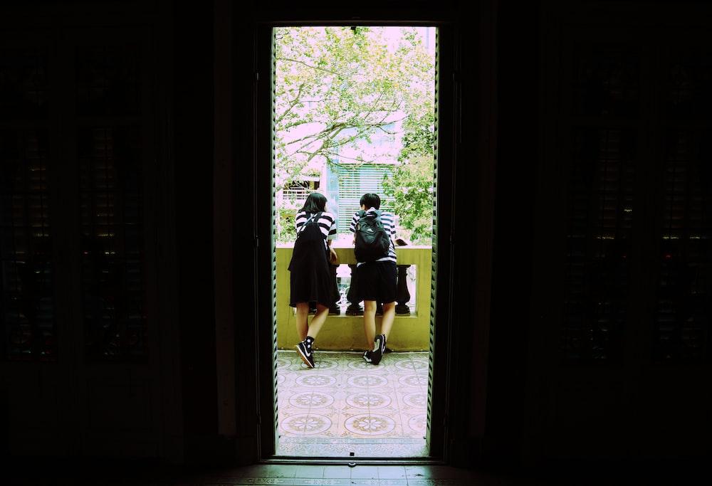 two women leaning on handrail