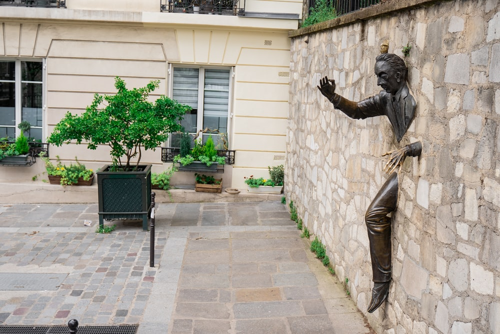 man trying to escape statue on wall
