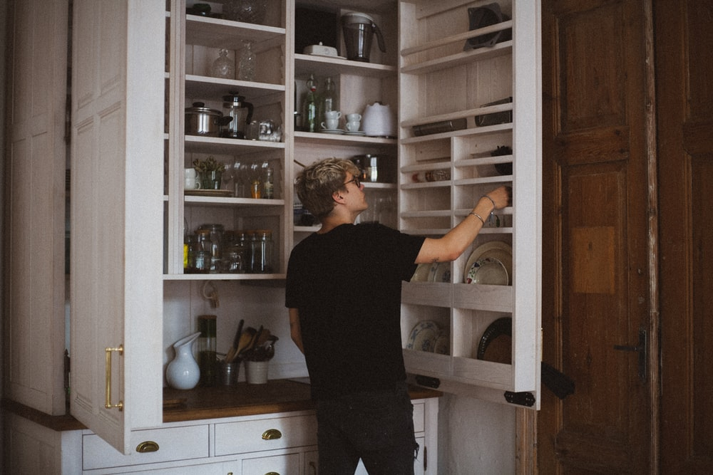 man standing near cabinet reaching plate